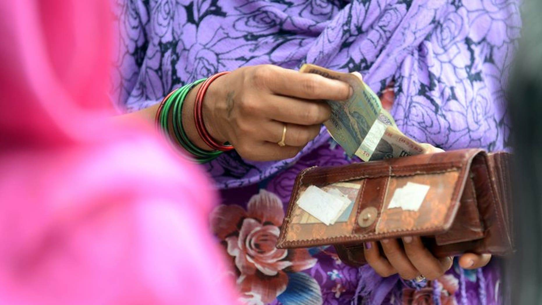 An Indian woman counts rupees to pay a vendor at a local market in New Delhi on August 17, 2013. India's premier ruled out Saturday any suggestion the country could suffer a repeat of its 1991 balance-of-payments crisis as it grapples with a plunging rupee and a huge trade gap.