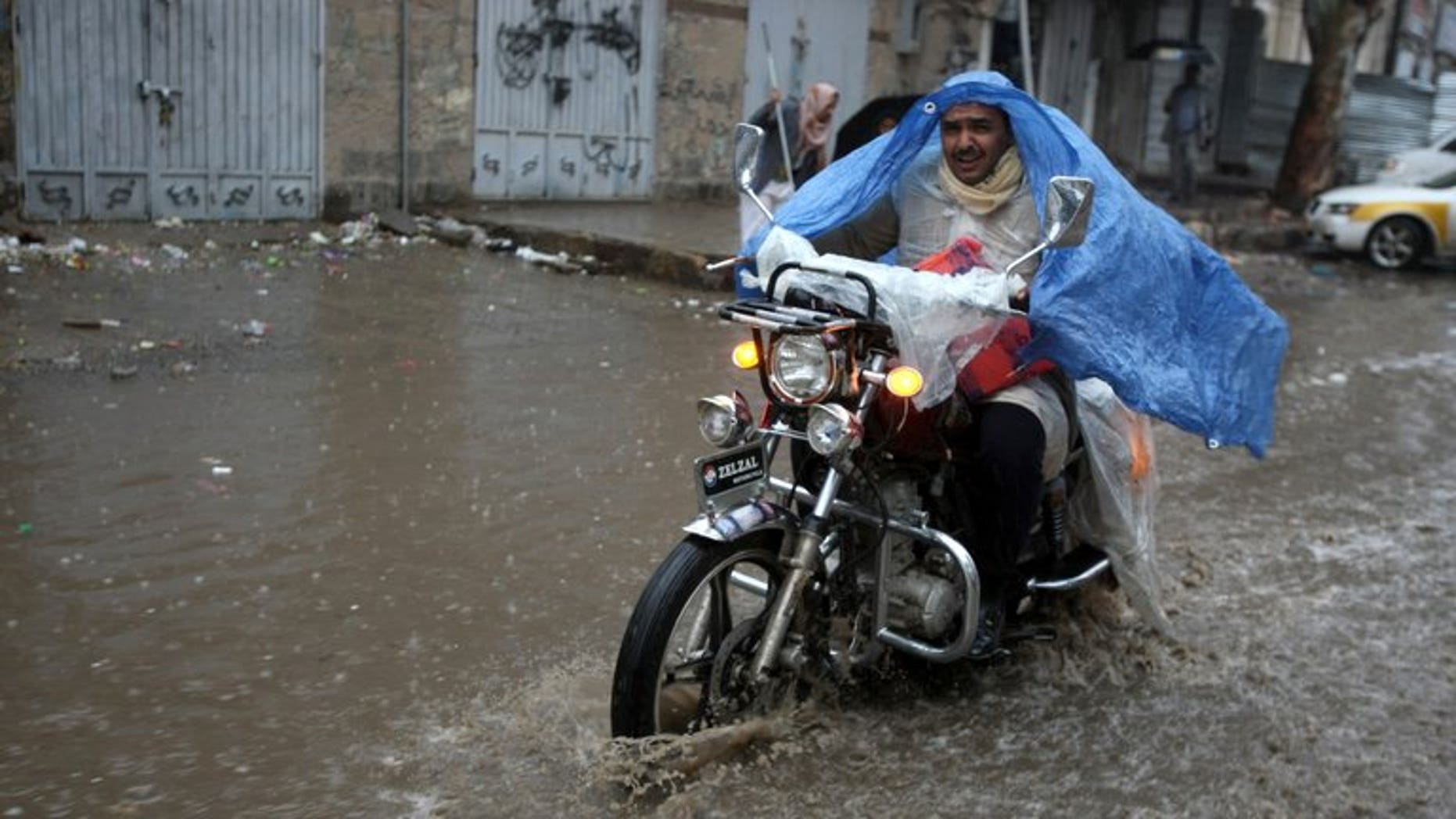 A Yemeni man rides his motorcycle through a flooded street following heavy rains in the capital Sanaa on April 9, 2012. Lightning and flash floods have killed 50 people in Yemen since Friday, including 27 who died when a torrent washed away a wedding convoy, local officials said Saturday.