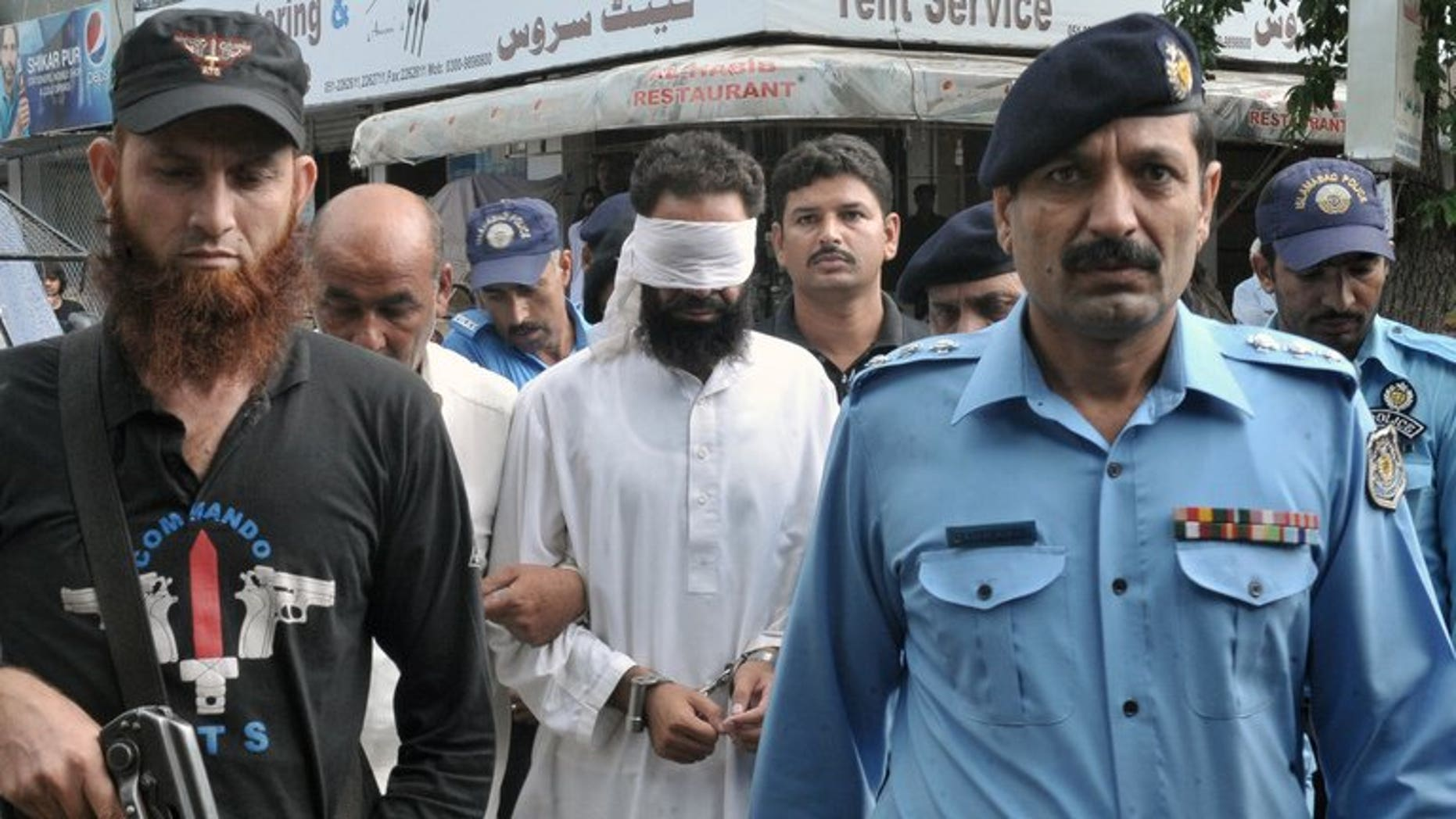 Pakistani policemen escort Islamic cleric Hafiz Mohammed Khalid Chishti (C) upon his arrival at a court in Islamabad on September 2, 2012. A Pakistan court on Saturday acquitted a Khalid Chishti, who accused a Christian girl of blasphemy before he himself was arrested on similar charges, a lawyer said.