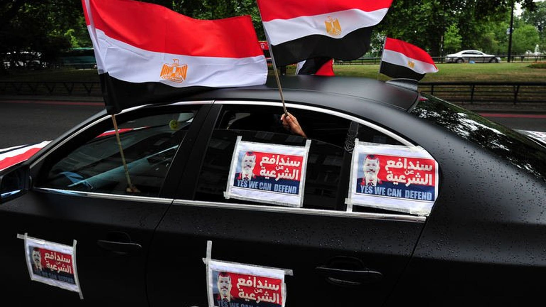 Demonstrators supporting Egypt's ousted Islamist president Mohamed Morsi hold Egyptian flags (L) from a car plastered with Morsi posters during a rally against the crackdown on protesters in Egypt in central London on August 17, 2013.