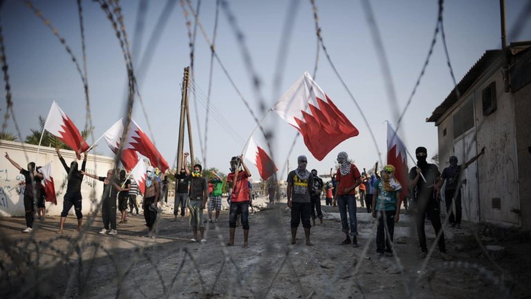Bahraini protestors wave their national flag as they stand behind barbed wire placed by riot police during demonstration against the ruling regime in the village of Shakhora, west of Manama, on August 14, 2013. Five Bahraini police were wounded late on Saturday, as security forces clashed with opposition protesters in a Shiite village north of the capital, police said.
