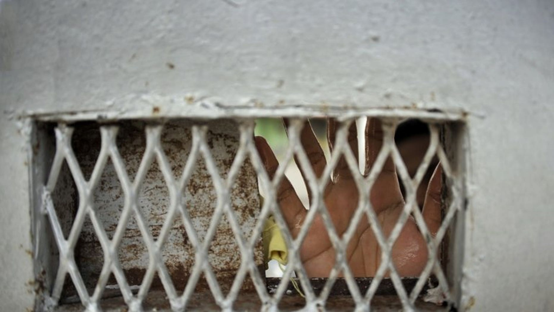 In this photograph taken on February 25, 2012, a prisoner's hands cover the window of an iron door of Kerobokan prison on Bali. About 30 prisoners escaped from an overcrowded jail on Indonesia's Sumatra island on Sunday after riots broke out, officials said.