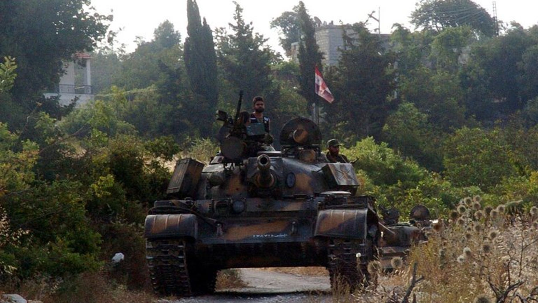 A handout picture released by the Syrian Arab News Agency (SANA) on August 8, 2013 shows Syrian army tanks parked on the side of a road during an alleged pursuit of opposition fighters in the Latakia province, western Syria. Fierce fighting raged in Latakia province on Syria's coastline on Sunday, as the army pushed an advance and killed a jihadist leader, a monitoring group said.