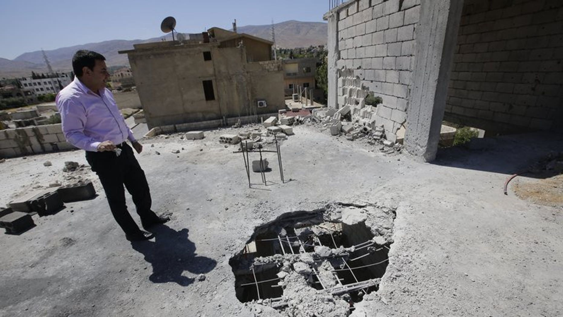 A Lebanese man inspects the damage after a rocket coming from Syria fell on his house in the town of Hermel, a few kilometres from Baalbek in the Bekaa valley, on April 26, 2013. Five rockets landed in and around the eastern Lebanese town of Hermel, a Hezbollah stronghold, on Sunday, a security source told AFP on condition of anonymity.