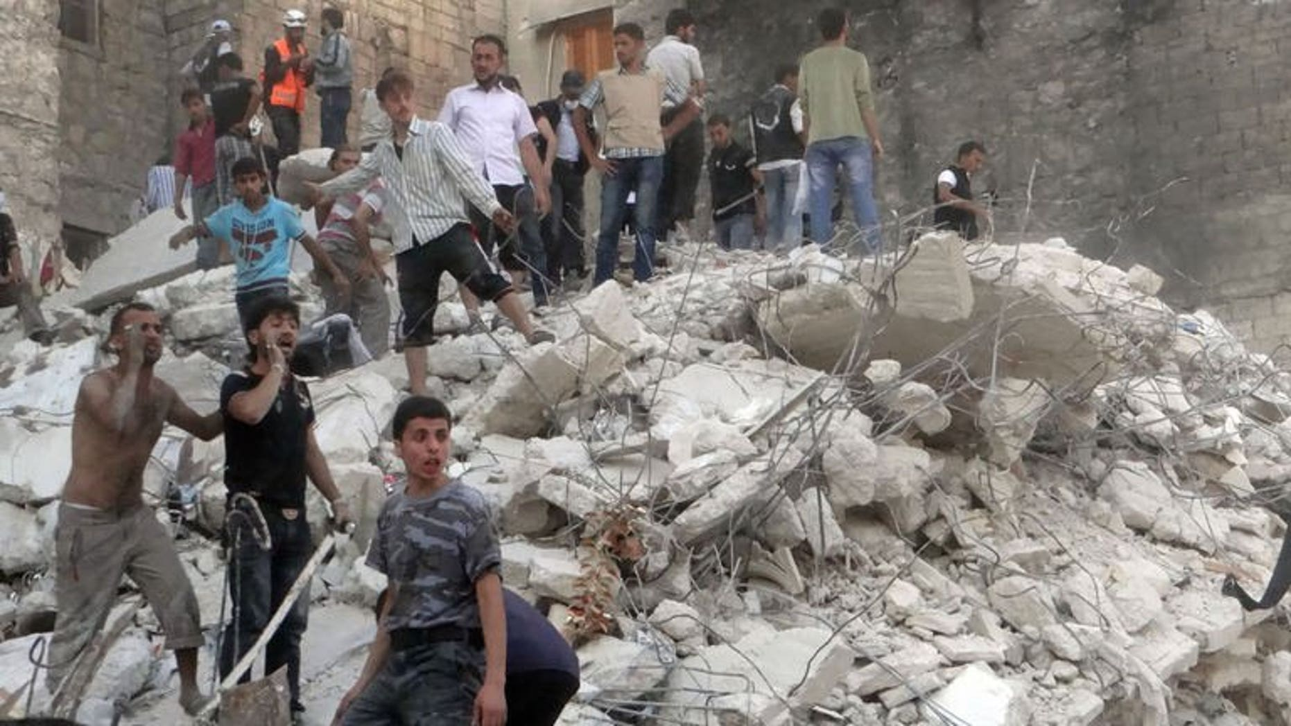"""Men stand on debris from a building which collapsed after it was allegedly bombed on August 16, 2013 in Aleppo. Syria's President Bashar al-Assad said on Sunday he is determined to """"eradicate terrorism"""" which he blames for the conflict raging in his country, according to state news agency SANA."""