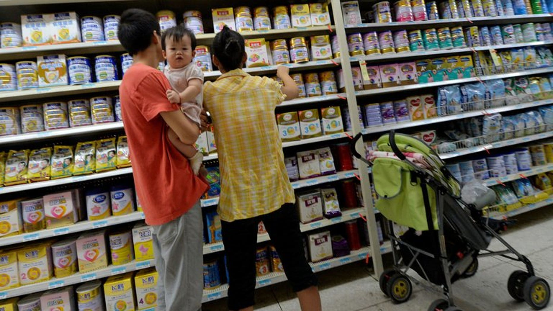 A Chinese family buys baby milk powder at a store in Beijing on August 7, 2013. The latest scare comes after an ingredient used in some baby formula contained a potentially deadly bug.