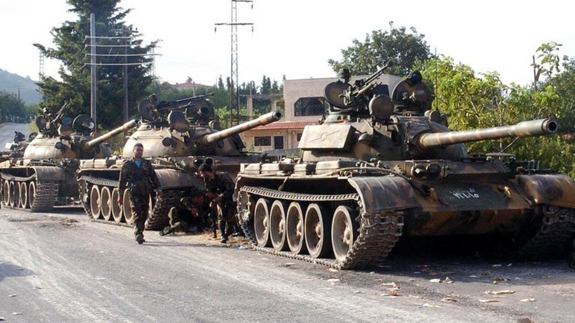 A picture released by the Syrian Arab News Agency (SANA) on August 8, 2013 shows Syrian army tanks parked on the side of a road during an alleged pursuit of opposition fighters in the Latakia province, western Syria. The Syrian army has recaptured all rebel-held positions in Latakia, President Bashar al-Assad's home province, state-run SANA news agency reported Monday quoting a military source.