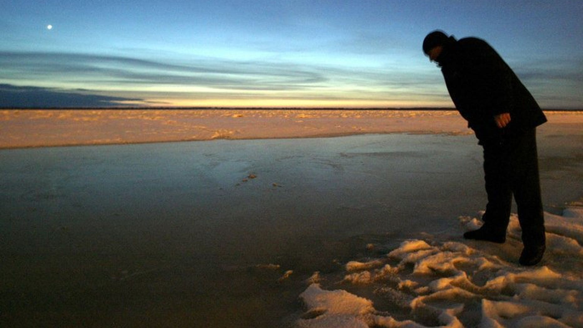 File picture shows a local resident looking into the Amur river in Khabarovsk, eastern Russia, December 24, 2005. Floods on the Amur River in Russia's Far East broke historic records Monday as authorities evacuated over 19,000 people from affected areas and warned of a further rise in water levels.