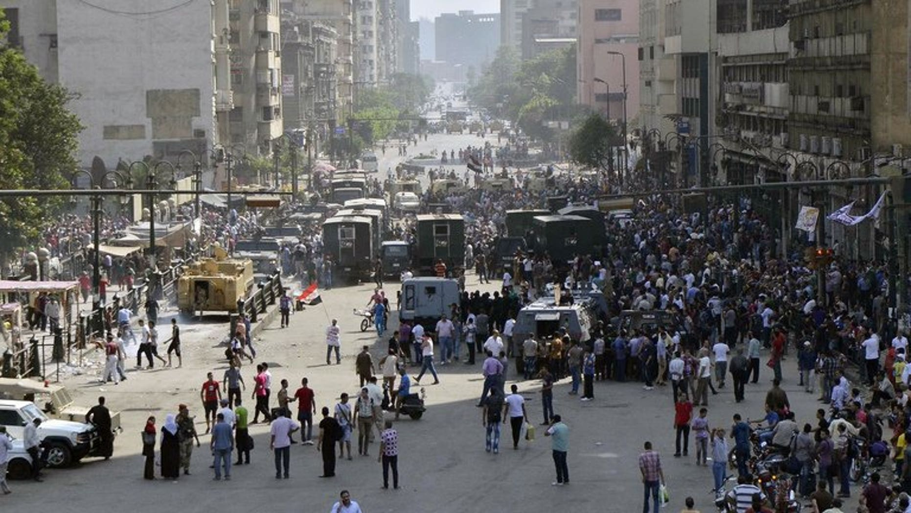 Egyptian demonstrators, soldiers and policemen gather outside Cairo's Al-Fath mosque on August 17, 2013. Two Canadians have been arrested in Egypt amid spiralling bloodshed in the Mideast nation, a Canadian official said Monday.