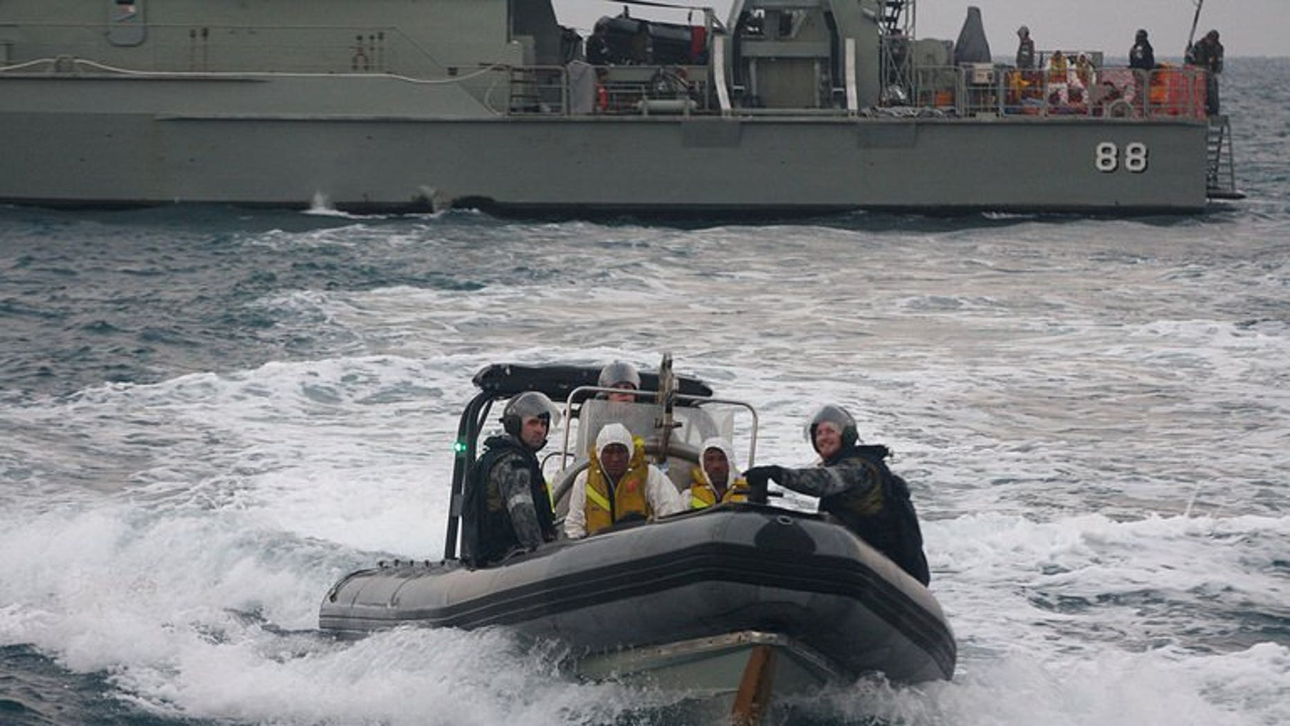 Australian navy personnel transfer asylum-seekers to a rescue boat near West Java on August 31, 2012. A rescue operation was underway Tuesday after an asylum-seeker boat started to sink off Christmas Island.