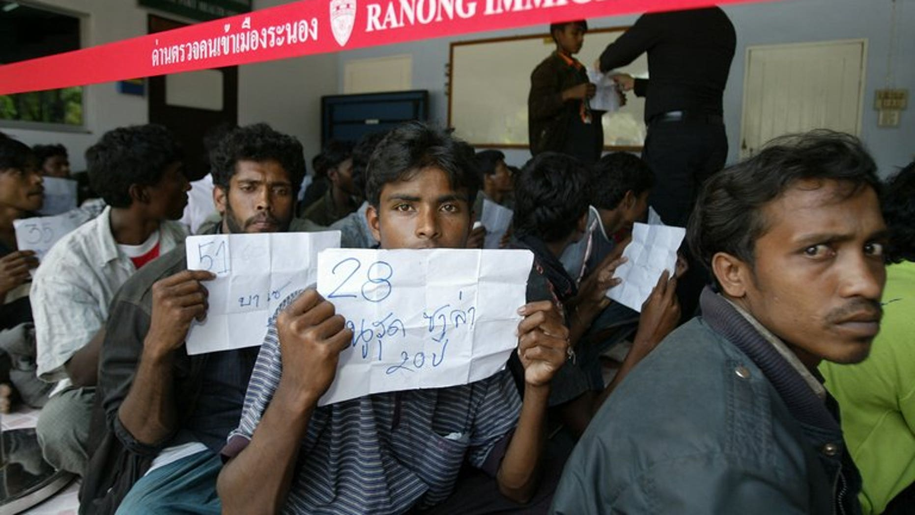 Rohingya migrants sit outside a police station before being transported to Thai police immigration on January 31, 2009. On Tuesday dozens escaped from a Thai immigration centre, police said.