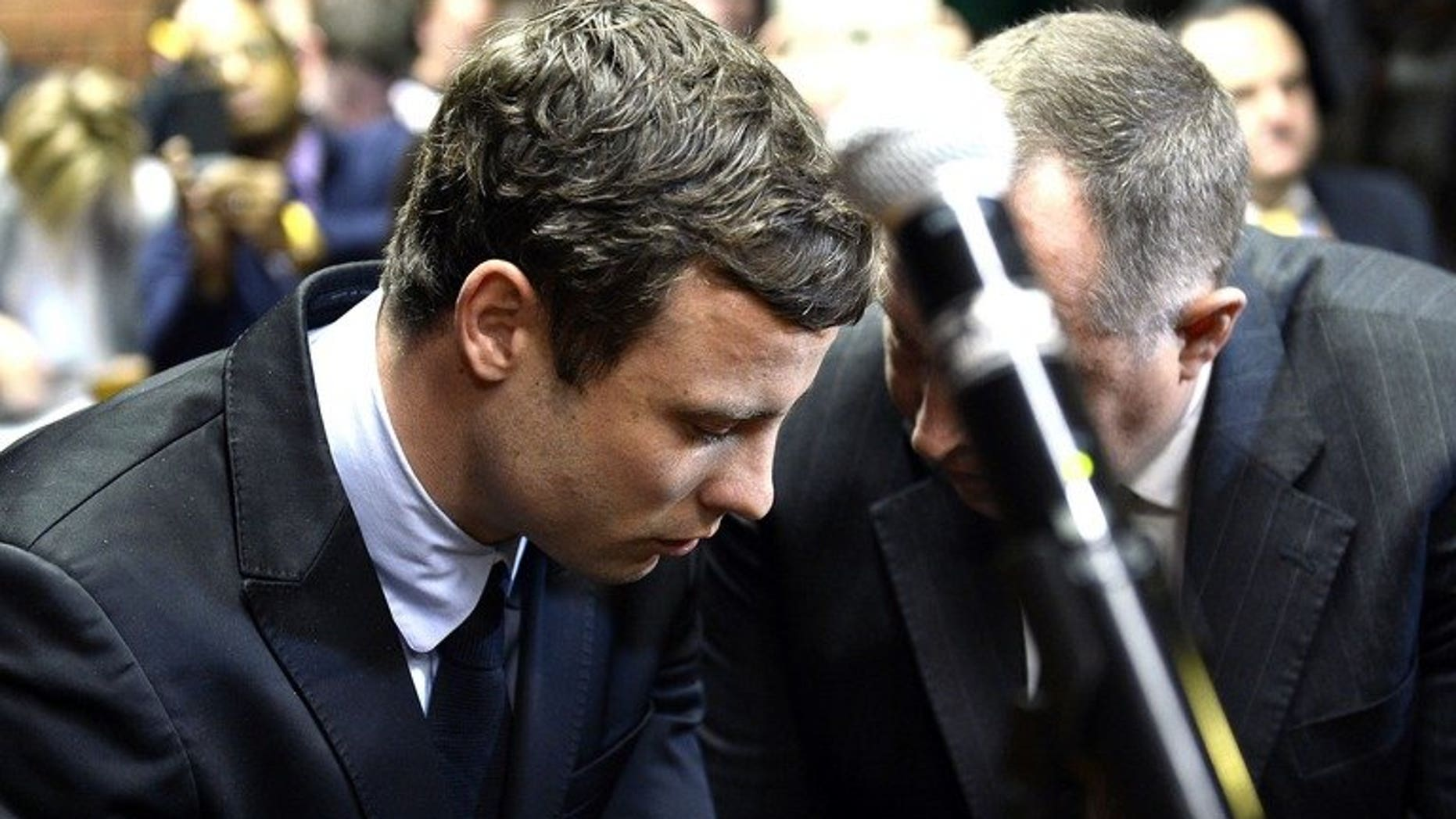 Oscar Pistorius (L) appears at Pretoria Magistrate's Court on August 19, 2013. South Africa's Paralympic sprint star has launched a bid to negotiate an out-of-court deal to pay damages to the parents of his lover whom he killed on Valentine's Day, a local newspaper says.