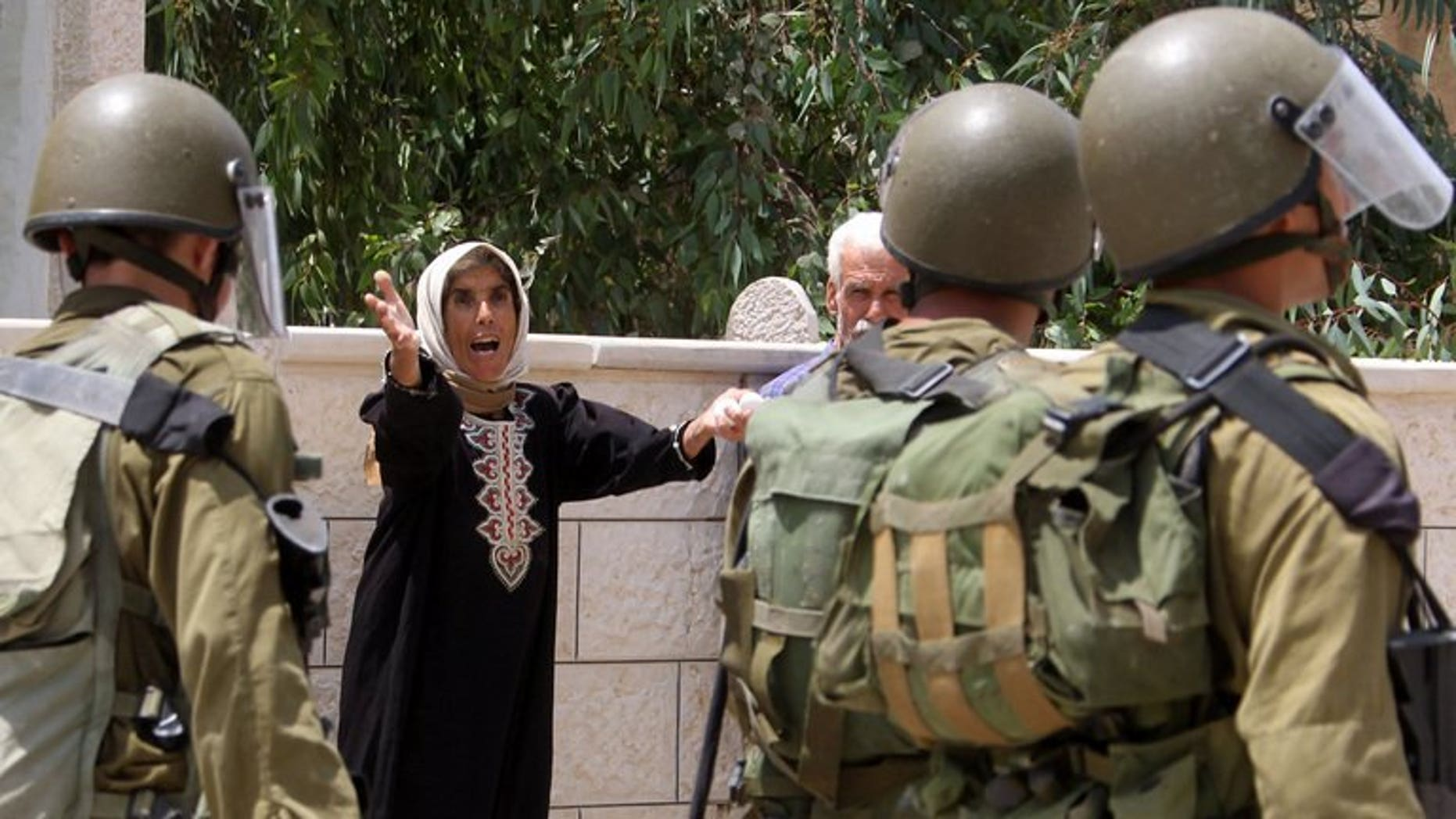 A Palestinian woman yells at Israeli soldiers during clashes following a protest in the village of Kfar Qaddum, near Nablus in the occupied West Bank on July 19, 2013. Israeli troops shot dead a Palestinian and wounded two others during an operation early Tuesday to arrest a Palestinian militant in the West Bank city of Jenin, the army said.