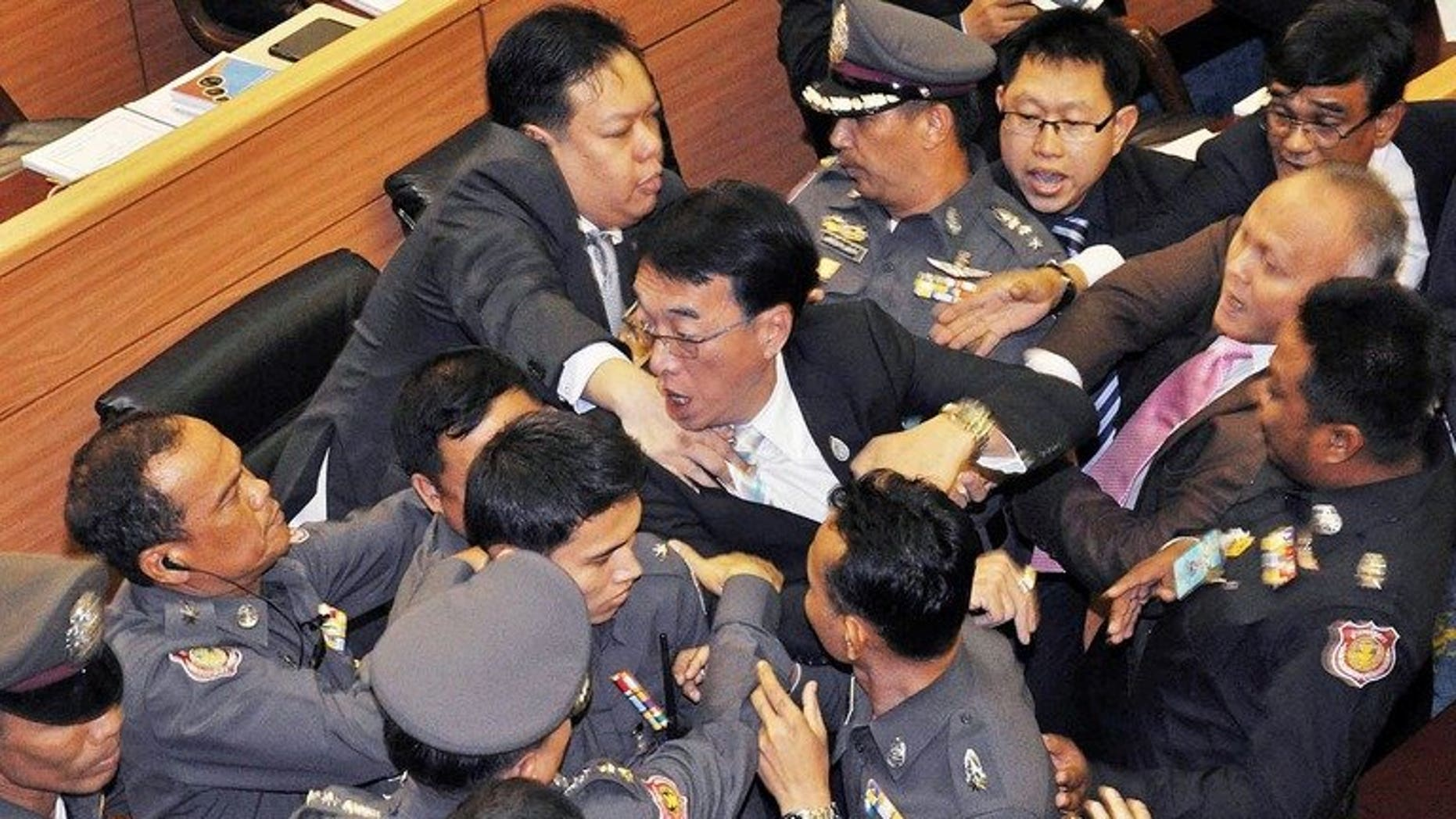 Members of the opposition Democrat party (C) are surrounded by parliament police officers during a brawl in parliament in Bangkok on August 20, 2013. Thailand's parliament briefly descended into chaos on Tuesday as opposition lawmakers brawled with police during a debate on controversial proposals to amend the constitution.