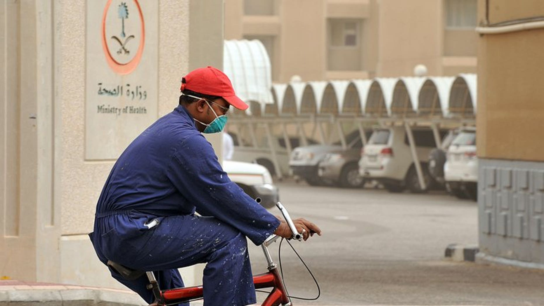 A foreign worker wears a mask as he rides a bicycle near the King Fahad hospital in the city of Hofuf on June 16, 2013. Health authorities in Qatar on Tuesday announced the first case of MERS coronavirus in the Gulf state, with a 59-year-old man infected.
