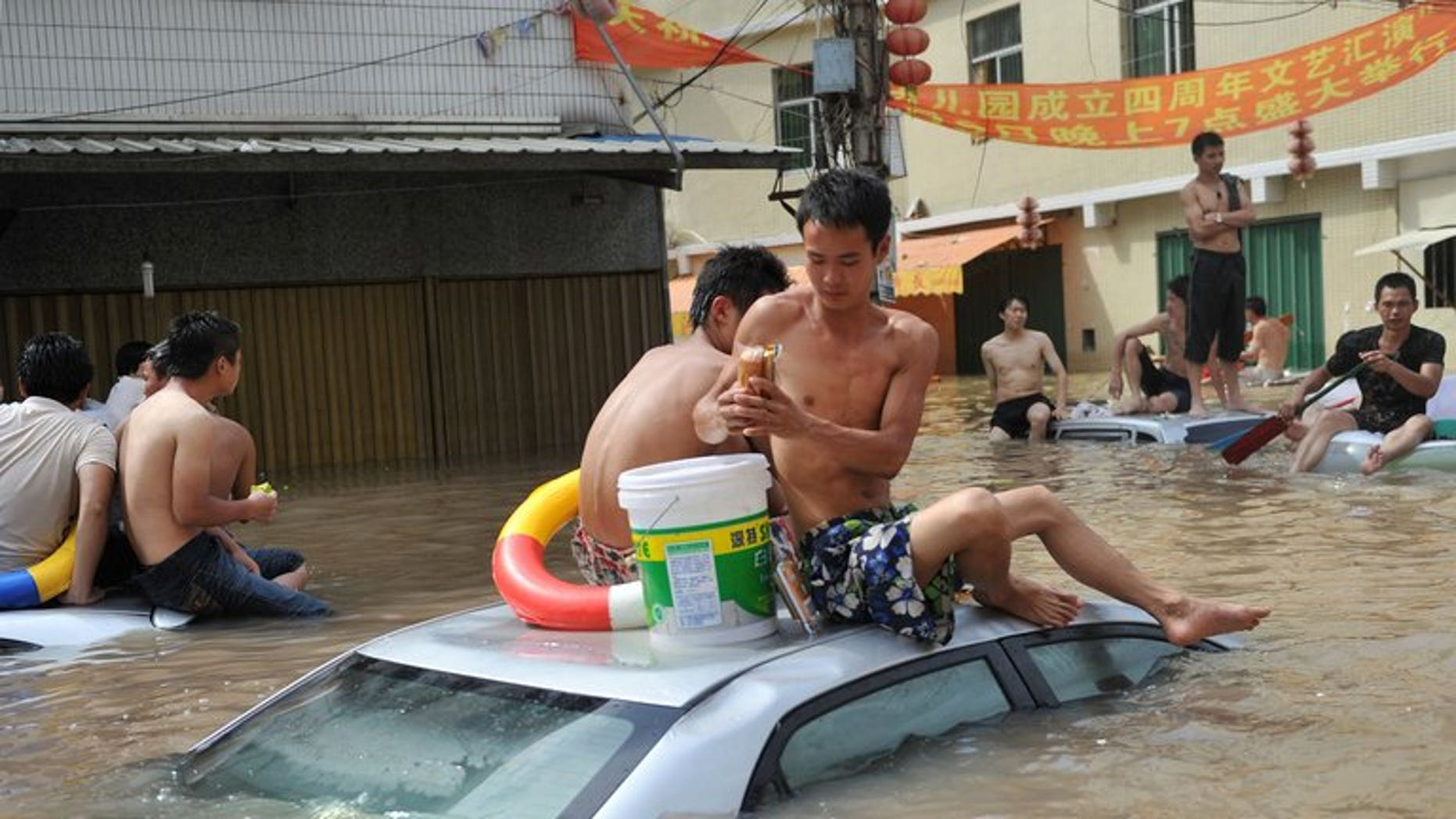 Residents sit on top of vehicles submerged by water in the flood-hit Chaonan district of Shantou, in southern China's Guangdong province, August 19, 2013. Heavy rains killed 21 construction workers as flooding spread to northwest China, state media said Wednesday, after severe weather in other parts of the country left more than 130 dead.