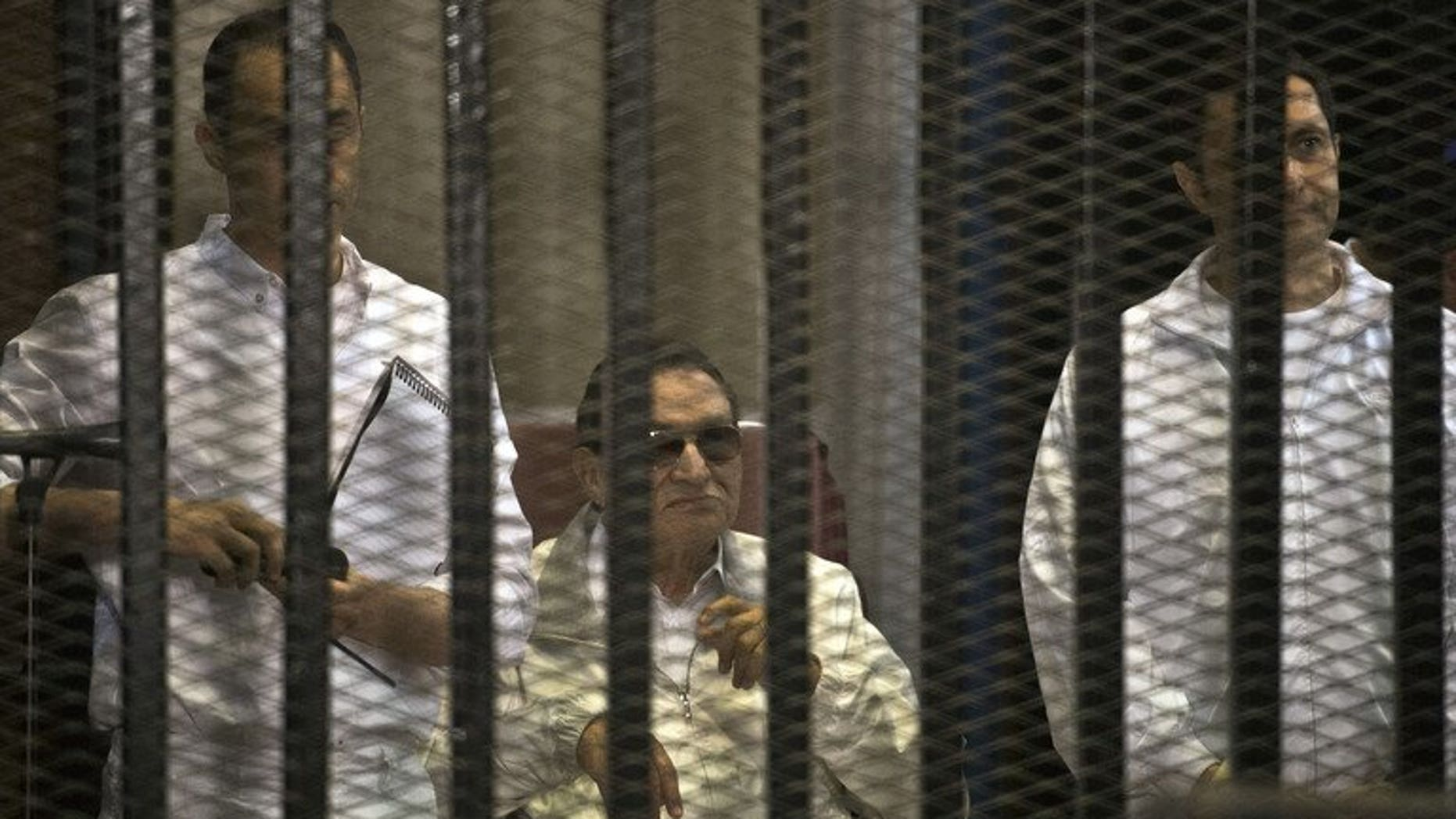 Ousted Egyptian president Hosni Mubarak (C) and his two sons Alaa (R) and Gamal during their retrial at the Police Academy in Cairo on June 8, 2013. Mubarak will face a new court hearing on Wednesday during which his lawyer will seek his release from prison, judicial sources said