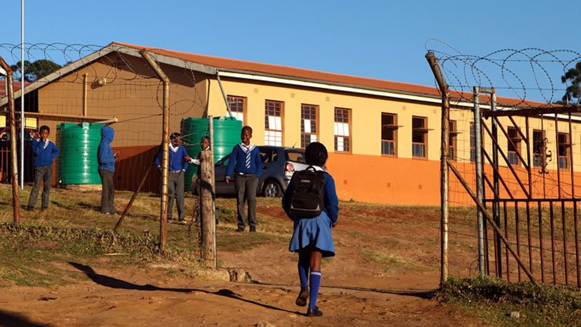 Children arrive at a South African village school on June 14. South African police conducting a nationwide sweep arrested six men suspected of producing and distributing child pornography as part of a global crime ring, a spokesman said Wednesday.
