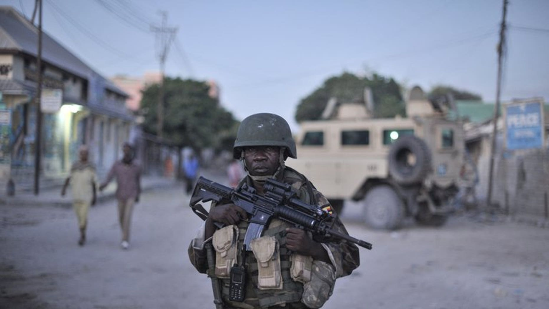 An AMISOM soldier monitors a street in Mogadishu. Gunmen killed two Somalis and wounded a Swedish woman in central Mogadishu on Wednesday when they opened fire on their car in the latest attack in the troubled city, police said.