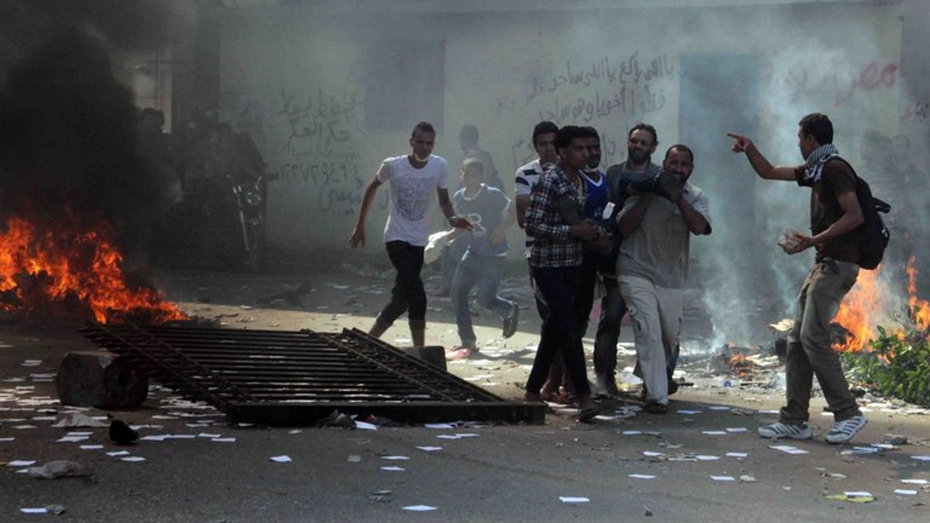 Egyptian Muslim Brotherhood supporters carry a wounded man in Cairo's Ramses square on August 16, 2013. EU foreign ministers Wednesday agreed to suspend the sale of security equipment and arms to Egypt, a statement said.