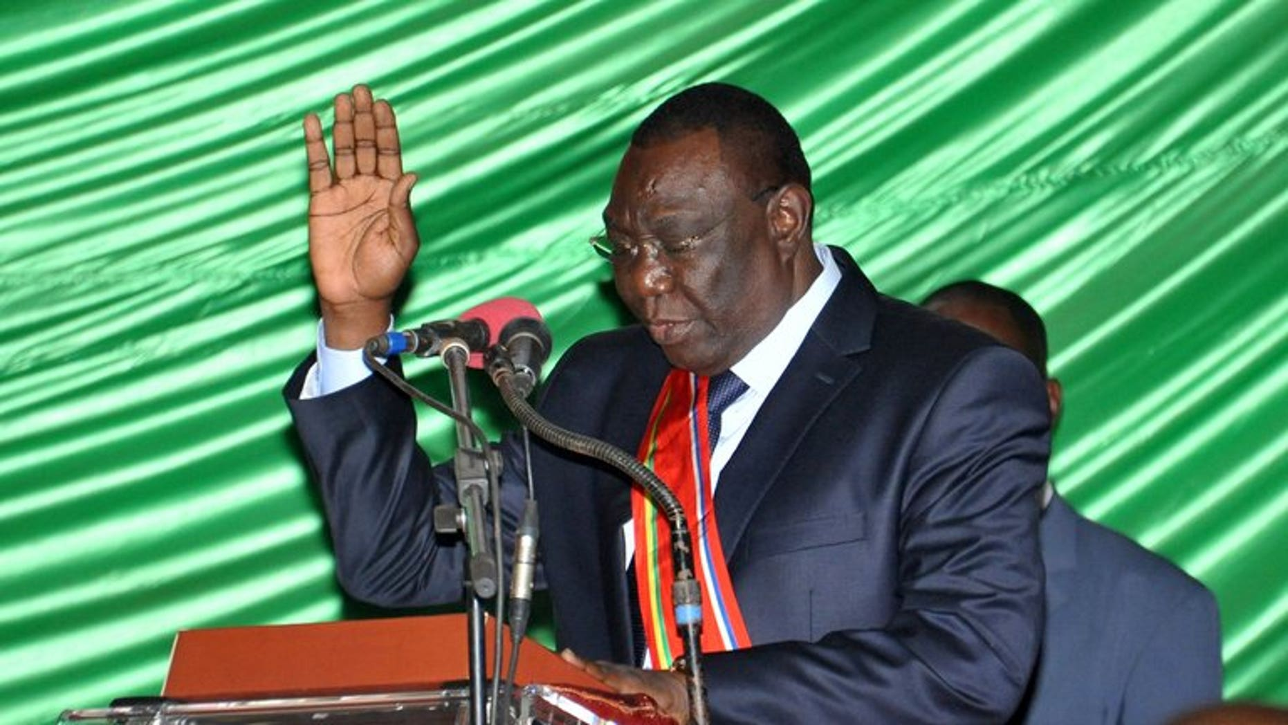 Former rebel leader Michel Djotodia takes the oath during a swearing-in ceremony on August 18, 2013 in Bangui. At least 11 people were killed and 35 injured in clashes that erupted when the new Central African Republic government tried to disarm supporters of ousted leader Francois Bozize, hospital sources said Wednesday.