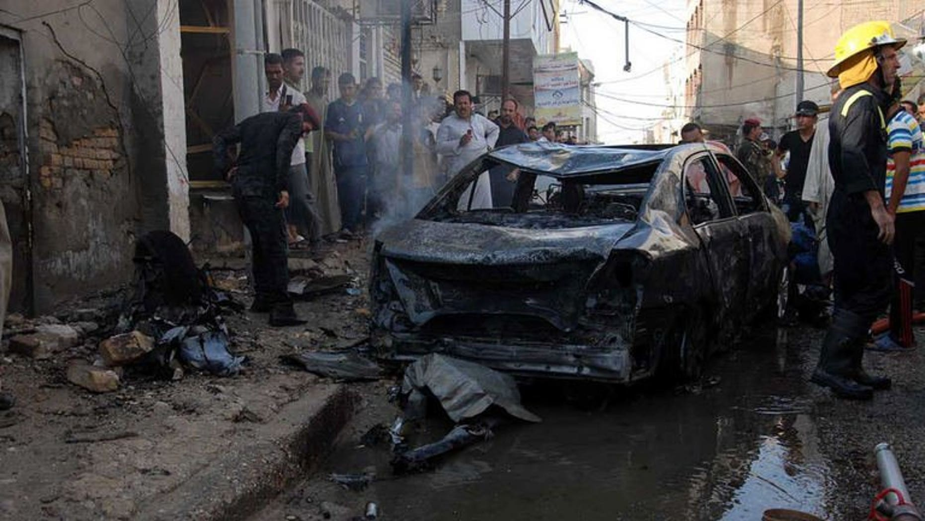 Iraqis gather near the remains of a vehicle at the scene of a car bomb in Nasiriyah, south of Baghdad on August 19, 2013. Attacks in Iraq killed seven people, damaged an oil pipeline and hit a Shiite shrine on Wednesday, as the country grapples with a months-long spike in violence.