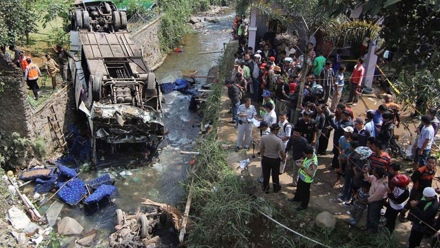 Indonesian police and officials examine the scene of an accident after a bus (L) plunged into a river in Cisarua, Bogor, in West Java on August 21, 2013. Eighteen people were killed and dozens injured Wednesday when a bus plunged into a river as it returned from a church outing on Indonesia's main island of Java, police said.