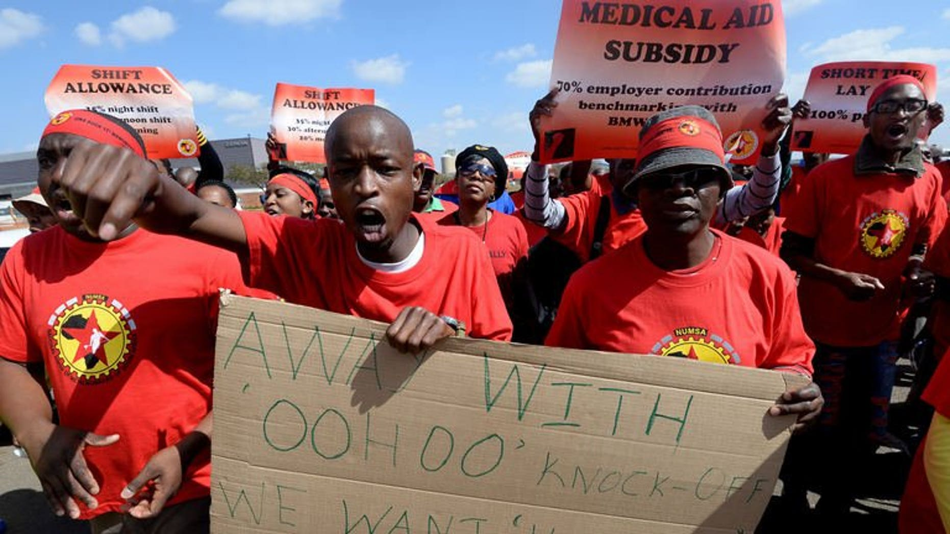 Workers on strike hold signs as they take part in a demonstration outside Ford's plant in Pretoria on August 20, 2013. A striking South African auto workers union will meet manufacturers on Thursday in a bid to break a wage deadlock that has crippled a multi-billion dollar export market.