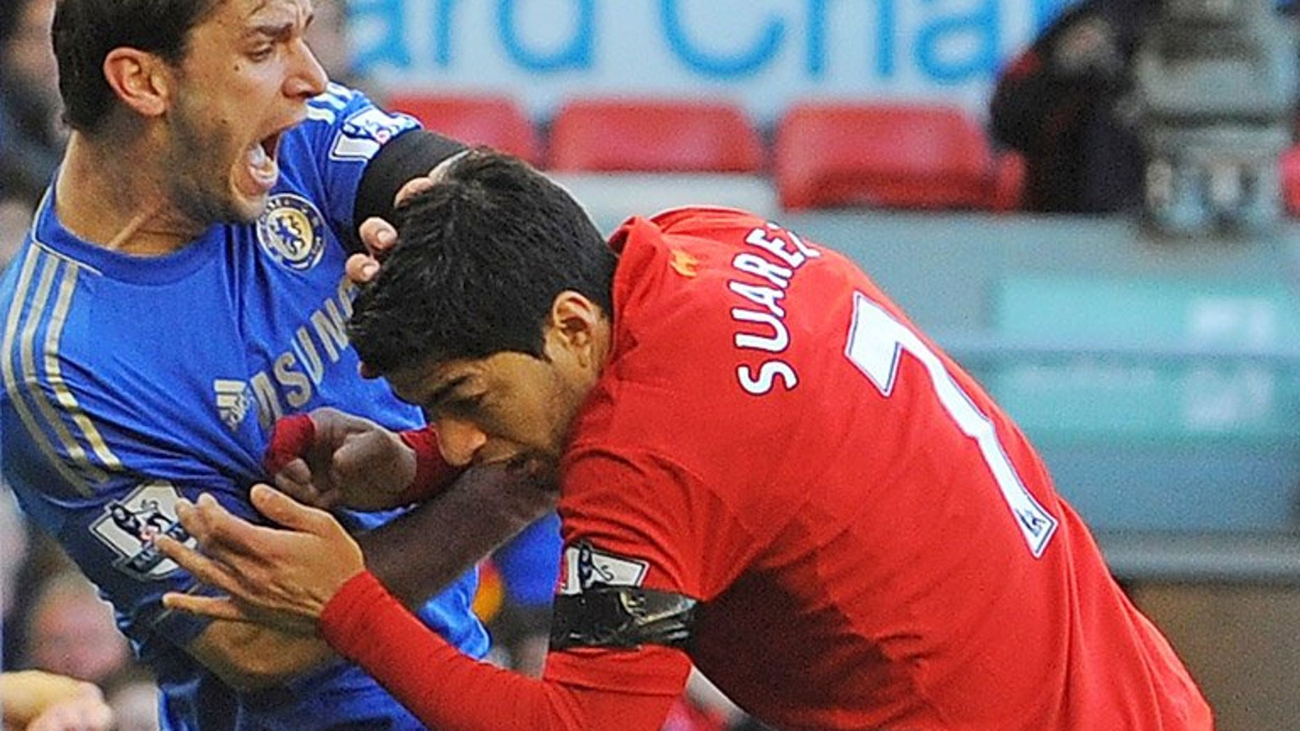 """Chelsea's Branislav Ivanovic (left) recoils after being bitten by Luis Suarez at Stamford Bridge on April 21. Arsenal manager Arsene Wenger has conceded defeat in his pursuit of Suarez after declaring there is """"no chance"""" Liverpool's Uruguayan striker will move to the Emirates Stadium."""