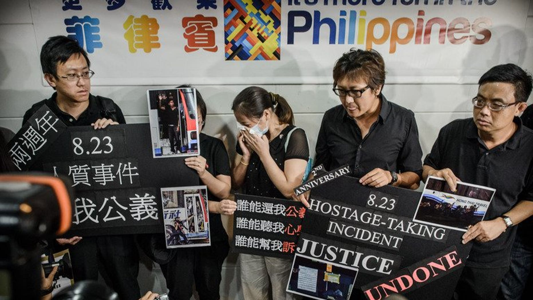 Survivors and relatives of eight Hong Kong tourists killed in a 2010 Philippine bus hostage fiasco gather outside the Philippines consulate in Hong Kong to demand an apology on August 23, 2012. Hong Kong survivors of a Manila hostage crisis and families of those killed sued the Philippine government Thursday to demand an apology and compensation, a day before the tragedy's third anniversary.