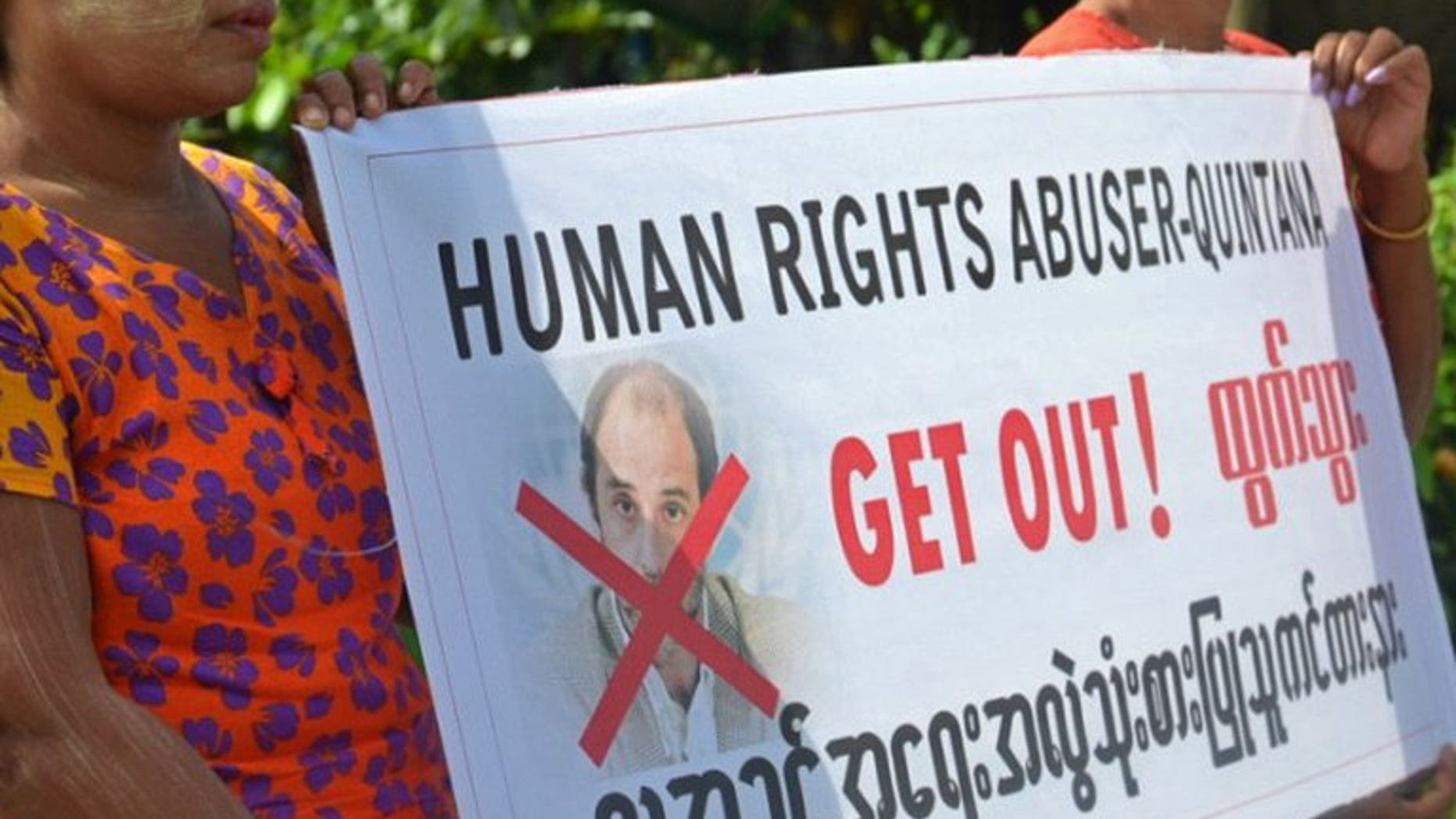 """Ethnic Rakhine villagers hold a placard as they demonstrate during the visit of UN human rights envoy Tomas Ojea Quintana in Sittwe, Myanmar on August 12, 2013. Myanmar police on Thursday rejected allegations that a convoy carrying a UN rights envoy though a town wracked by religious unrest was attacked by a mob, blaming a """"misunderstanding"""" for the incident."""