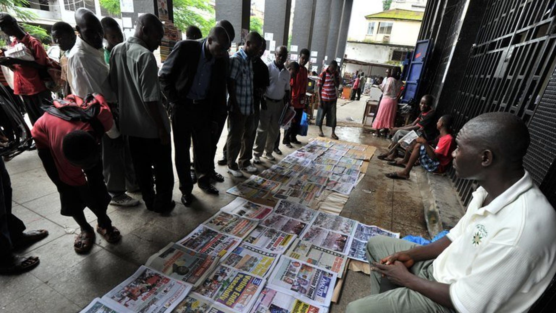 People look at newspapers laid out on the street in the Liberian capital Monrovia on October 12, 2011. The publisher of one of Liberia's leading local daily newspapers has been jailed for libel over a report about government corruption, according to an AFP correspondent at the court, sparking outrage in Monrovia.