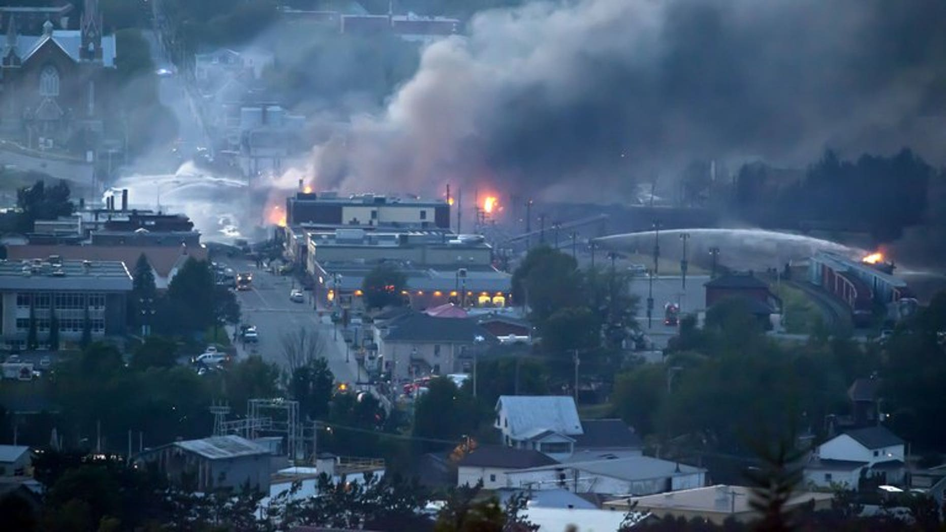 Firefighters douse blazes after a freight train loaded with oil derailed in Lac-Megantic in Canada's Quebec province on July 6, 2013. Canada's Senate called for a full safety review of pipelines, railroads and other means of transporting crude oil, in a report Thursday that also urges better responses to spills.