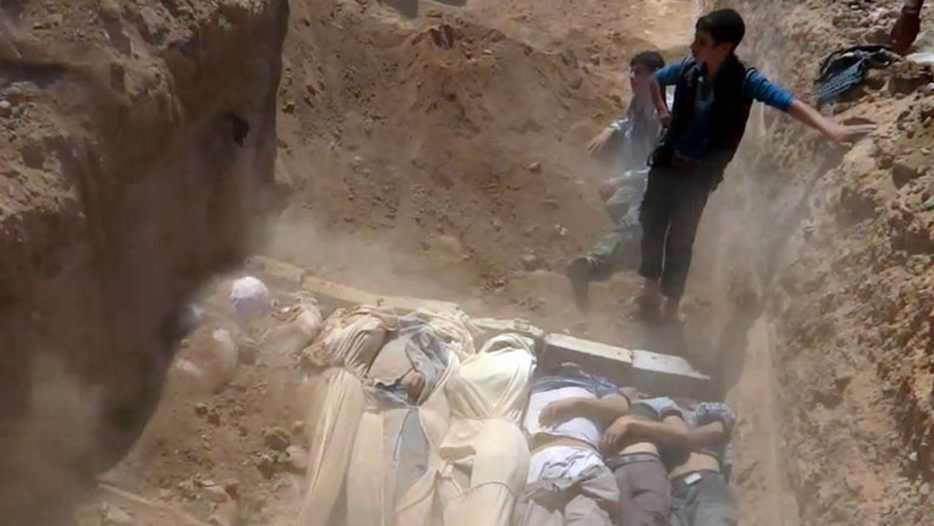 An image grab taken from a video uploaded on YouTube by the Local Committee of Arbeen on August 21, 2013 allegedly shows Syrians covering a mass grave with bodies of victims of a toxic gas attack. The convulsions, pinpoint pupils and laboured breathing seen in victims of the alleged chemical attack could be symptoms of nerve gas, experts say, but only blood and urine samples can provide proof.
