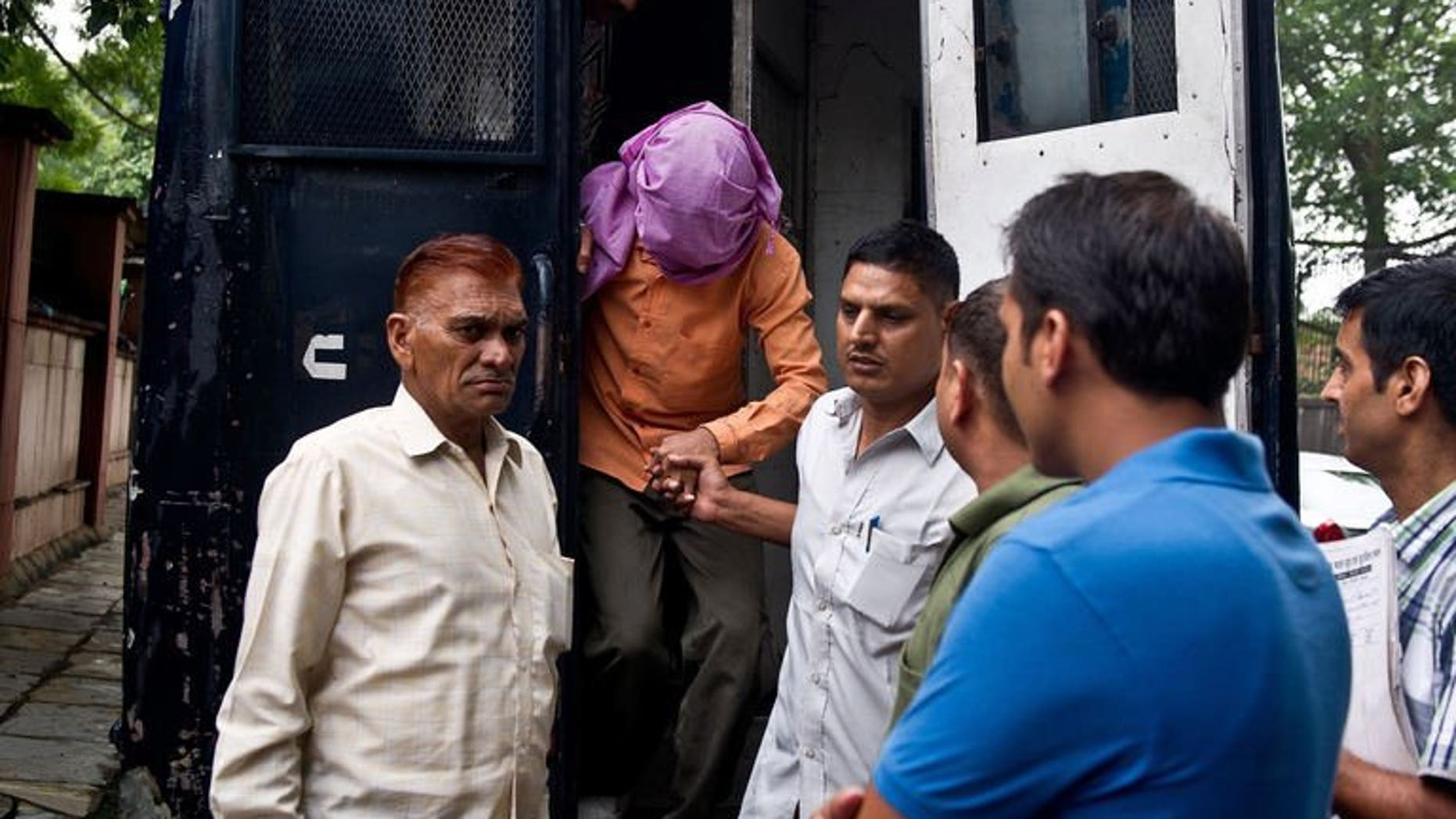 Indian policemen escort the juvenile accused (2nd L) in the December 2012 gang-rape of a student, from a police vehicle outside the juvenile court in New Delhi on August 19, 2013. The trials of five suspects for the fatal gang-rape of an Indian student on a bus last December moved towards their conclusions on Thursday, with the first verdict set for August 31.