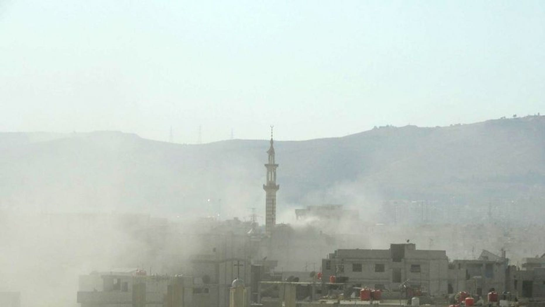A handout image released by the Syrian opposition's Shaam News Network shows smoke above buildings following what Syrian rebels claim to be a toxic gas attack by pro-government forces in eastern Ghouta, on the outskirts of Damascus on August 21, 2013.
