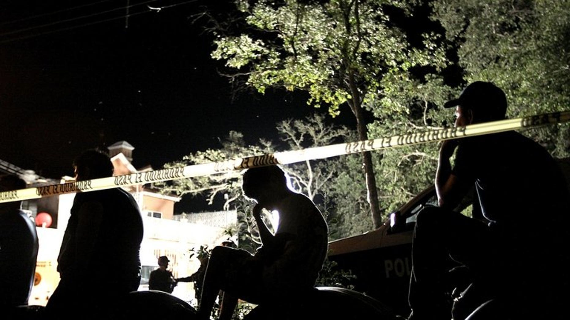 People observe police at a crime scene in Mexico on October 22, 2012. Mexican authorities are investigating whether human remains found in a park outside the capital belong to 12 young people whose kidnapping in May shocked the city, officials said Thursday.