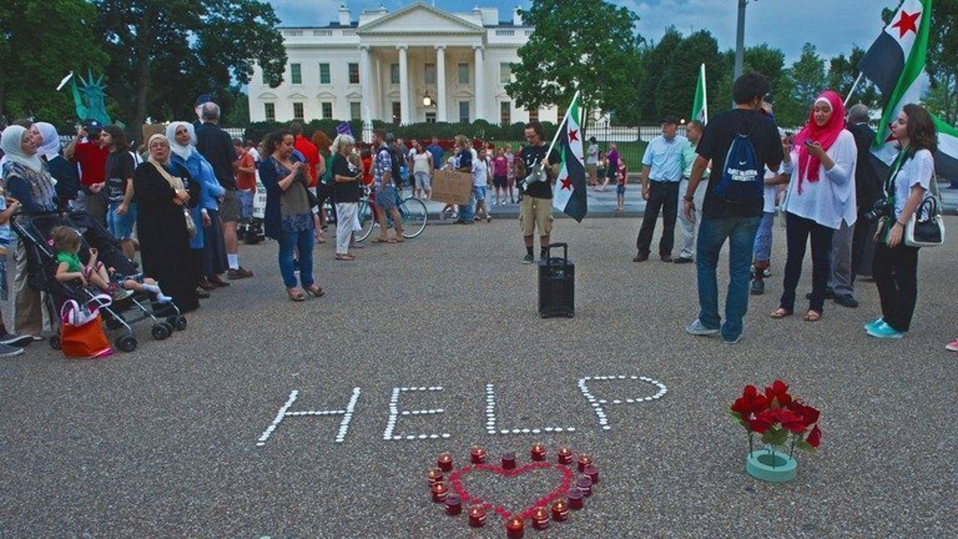 """Demonstrators calling for help from US President Obama on the Syrian revolution protest in front of the White House on August 21, 2013, in Washington, DC. A year after Washington said using chemical weapons would cross a """"red line,"""" the alleged gas attack outside Damascus has exposed how few options the West has to try to end Syria's violence."""