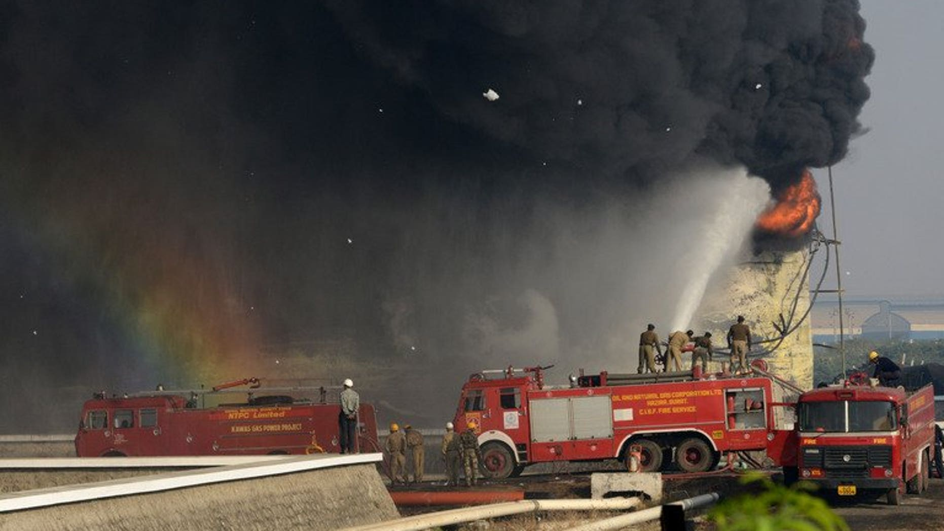 Indian firefighters battle to douse the flames of a burning fuel tank at the Indian Oil Corporation plant at Hajira near Surat, some 275 kms from Ahmedabad, on January 6, 2013. A massive fire broke out Friday at a petroleum refinery in southern India, killing four workers and leaving dozens injured, police said.
