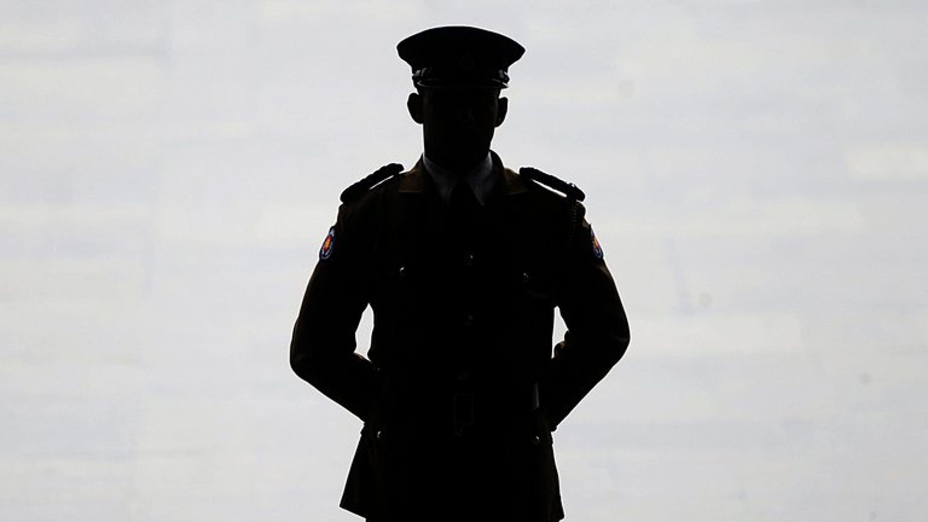 A Sri Lankan police officer keeps watch at parliament in Colombo on May 31, 2013. Sri Lanka's president has bowed to international pressure and relinquished the defence ministry's authority over the police department, an official said Friday.