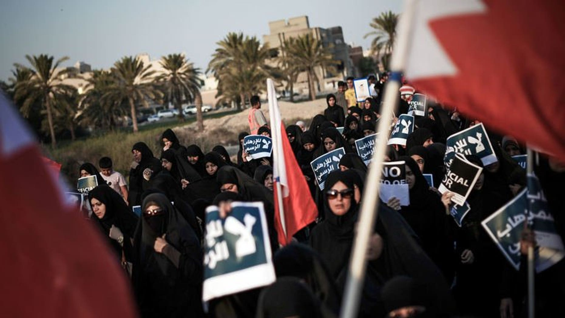 Bahraini women carry posters during an anti-government rally in the village of Abu Saiba, west of Manama, on August 23, 2013. Shiite protesters took to the streets in Bahrain Friday demanding political reforms in the Sunni-ruled Gulf kingdom, witnesses said.