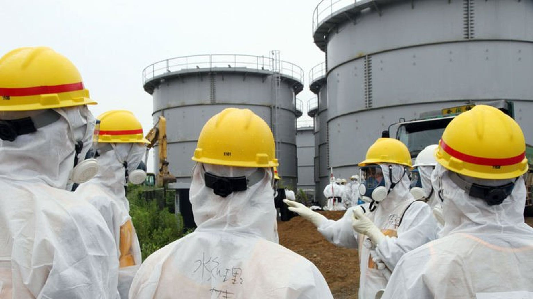 Japan's nuclear watchdog members, including Nuclear Regulation Authority members in radiation protection suits, inspect contaminated water tanks at the Tokyo Electric Power Co (TEPCO) Fukushima Dai-ichi nuclear power plant in the town of Okuma, Fukushima prefecture on August 23, 2013.