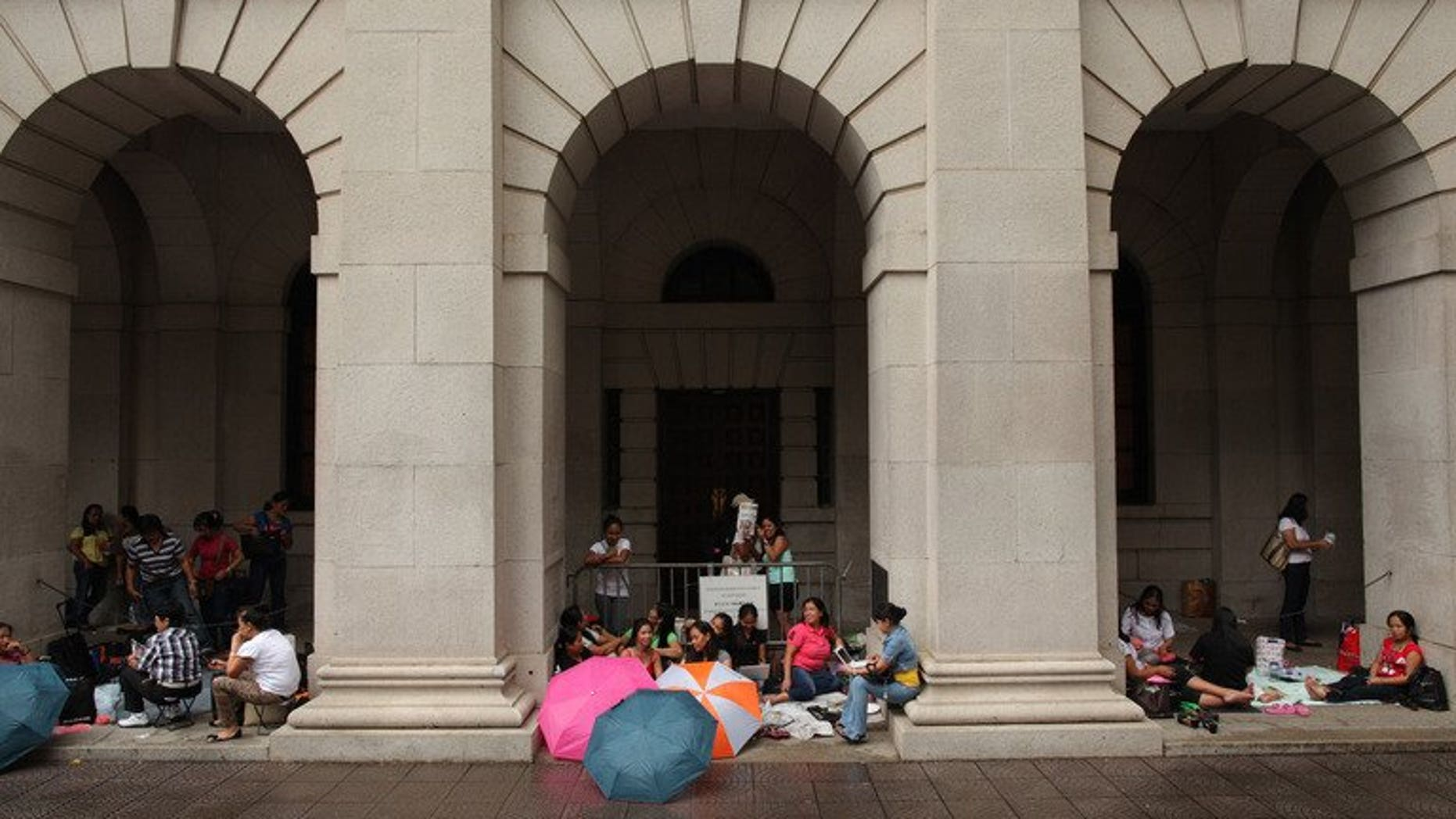 Foreign domestic helpers sit beneath the arches of the former Legislative Council building in Hong Kong on October 2, 2011. A Hong Kong couple left their Indonesian domestic helper without food or water after tying her to a chair and forcing her to wear a diaper while they went on five-day vacation, a report said Saturday.