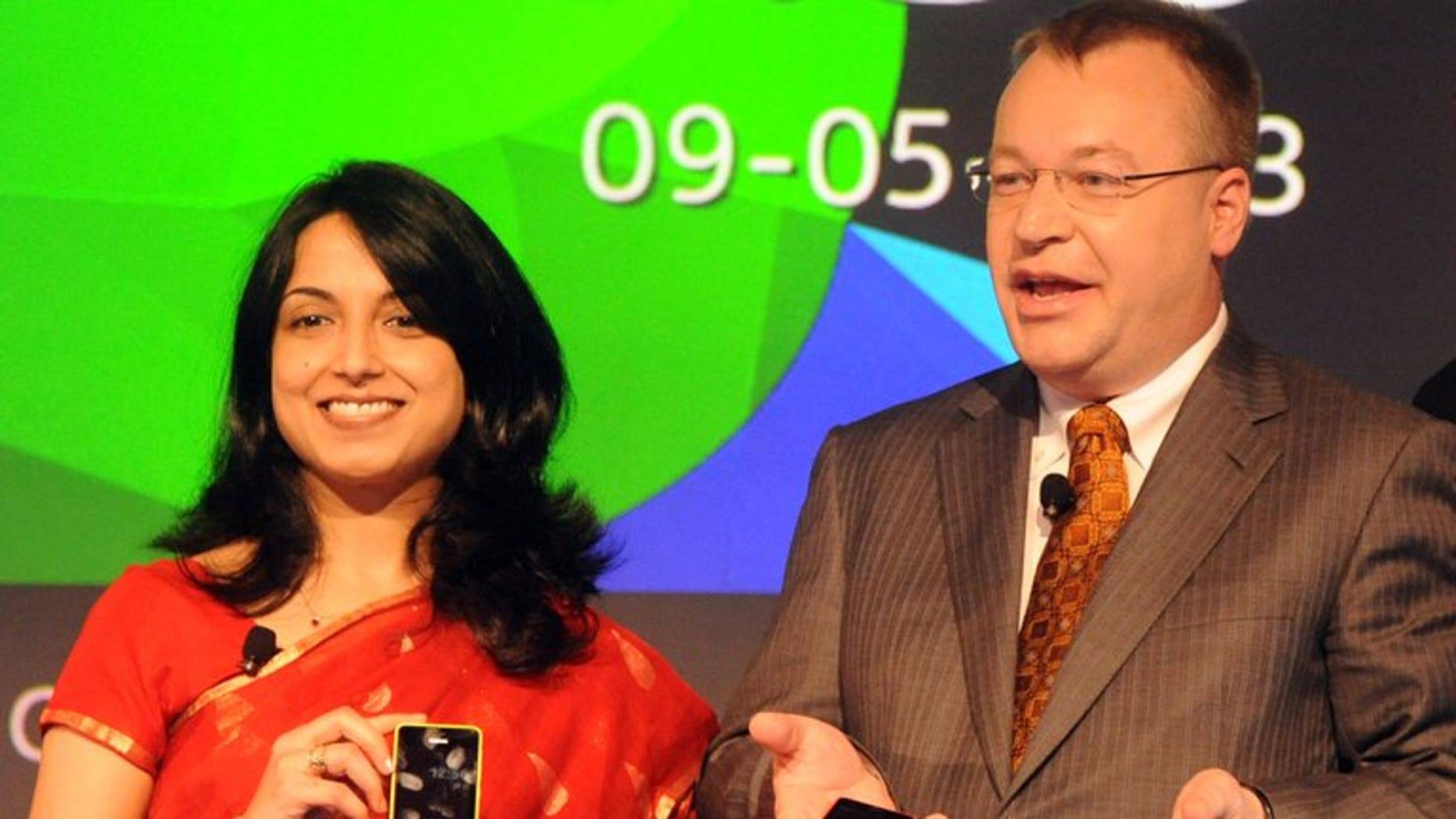 """Nokia Corporation, CEO, Stephen Elop (right) and Head-Developer Outreach of Nokia, Sangeeta Bavi hold Nokia Asha 501 cellular telephones in New Delhi on May 9, 2013. The Finnish telecom giant said Saturday it is in talks with India's government about how to create a better business climate and remains """"committed"""" to its manufacturing plant in the country."""
