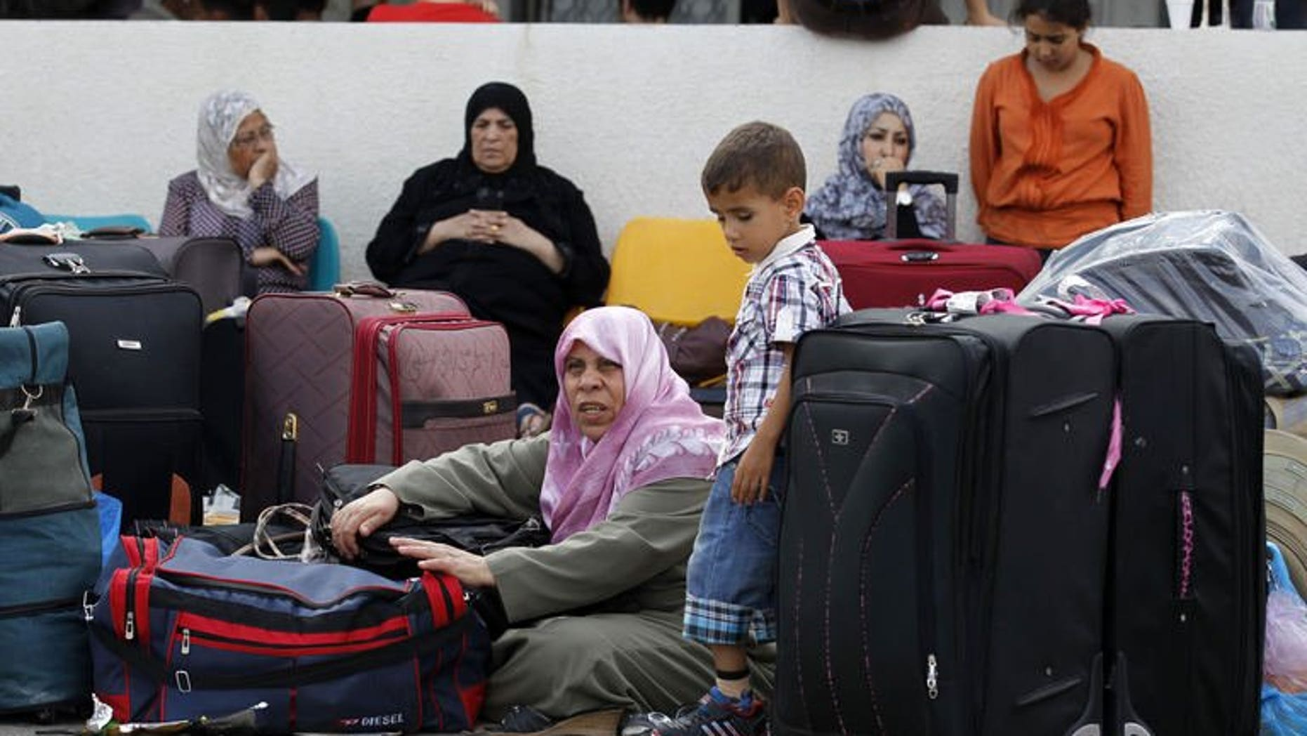 Palestinians wait at the Rafah border terminal in the southern Gaza Strip before crossing into neighbouring Egypt on August 24, 2013.