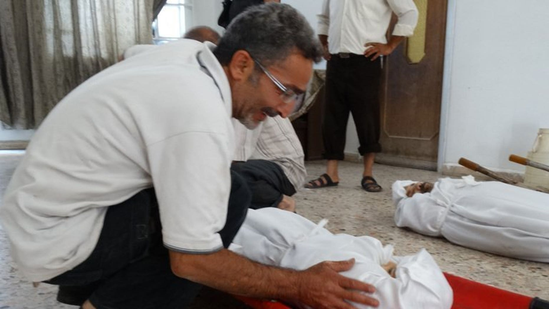 """An image released by the Syrian opposition's Shaam News Network on August 23, 2013, shows a relative weeping over the body of an infant killed in an alleged toxic gas attack. Three Syrian hospitals have received around 3,600 patients displaying """"neurotoxic symptoms"""", 355 of whom have died, Doctors without Borders (MSF) say."""