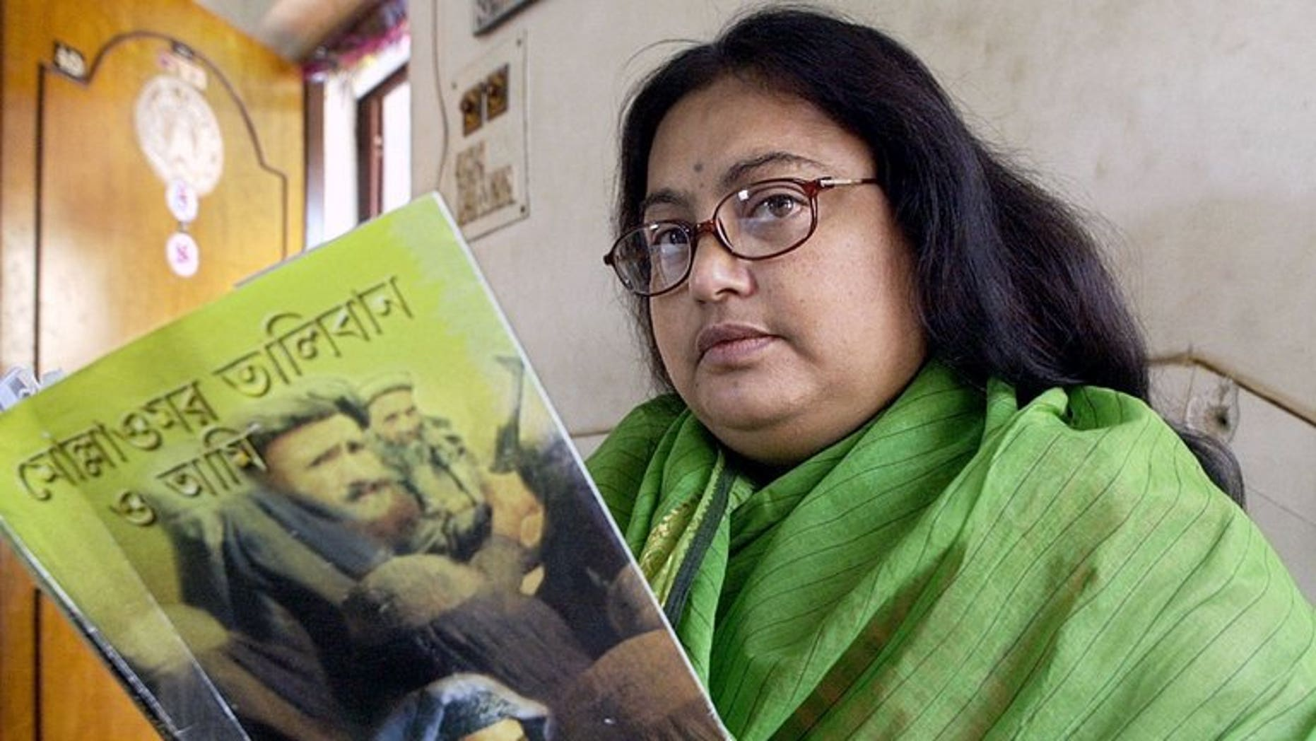 """In this photograph taken on March 6, 2003, Indian author Sushmita Banerjee holds one of her Bengali language novels """"Mollah Omar Taliban O Aami"""" (Mollah Omar, Taliban and Me) in Kolkata. Suspected Taliban militants have shot dead Banerjee in the eastern Afghan province of Paktika, police said."""