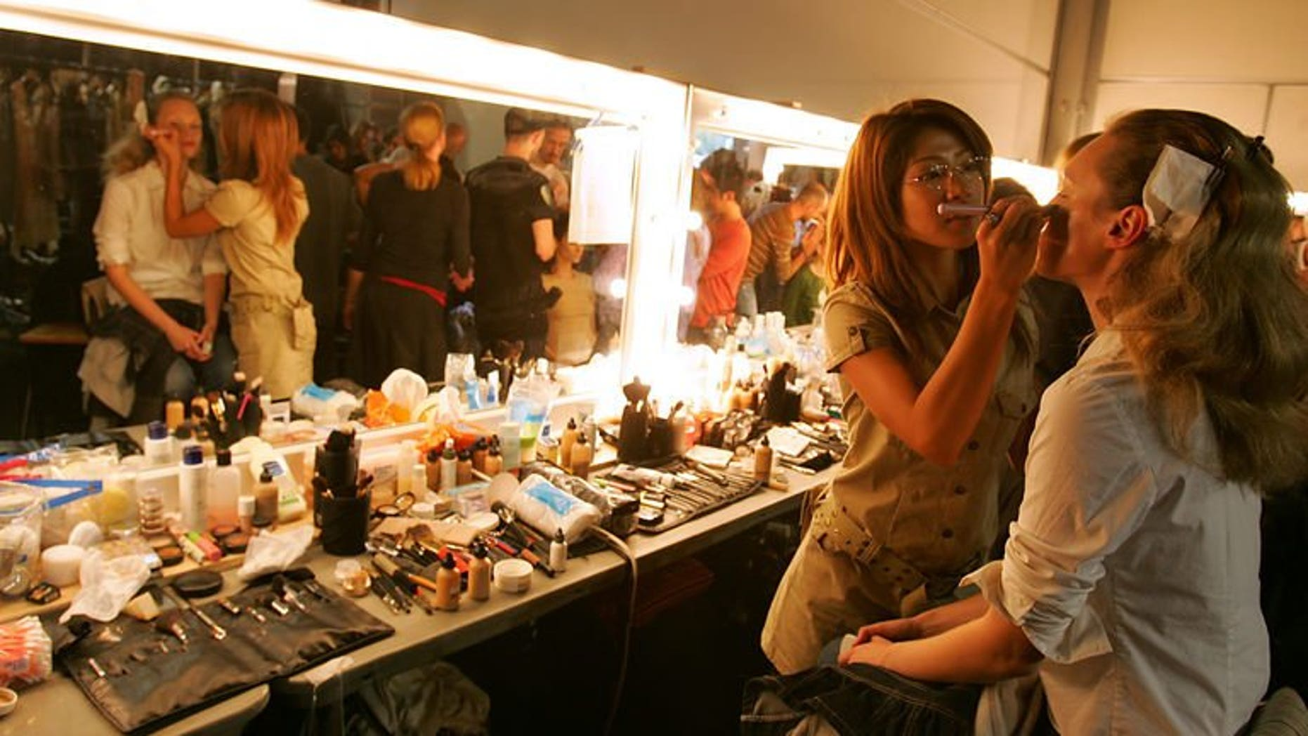 Models have final touches put to their hair and make-up in London, on September 19, 2005. Their skin is flawless, their make-up perfect and their hair sleek, but to teenage girls hoping to emulate fashion models, British Vogue has a message -- it's not real.