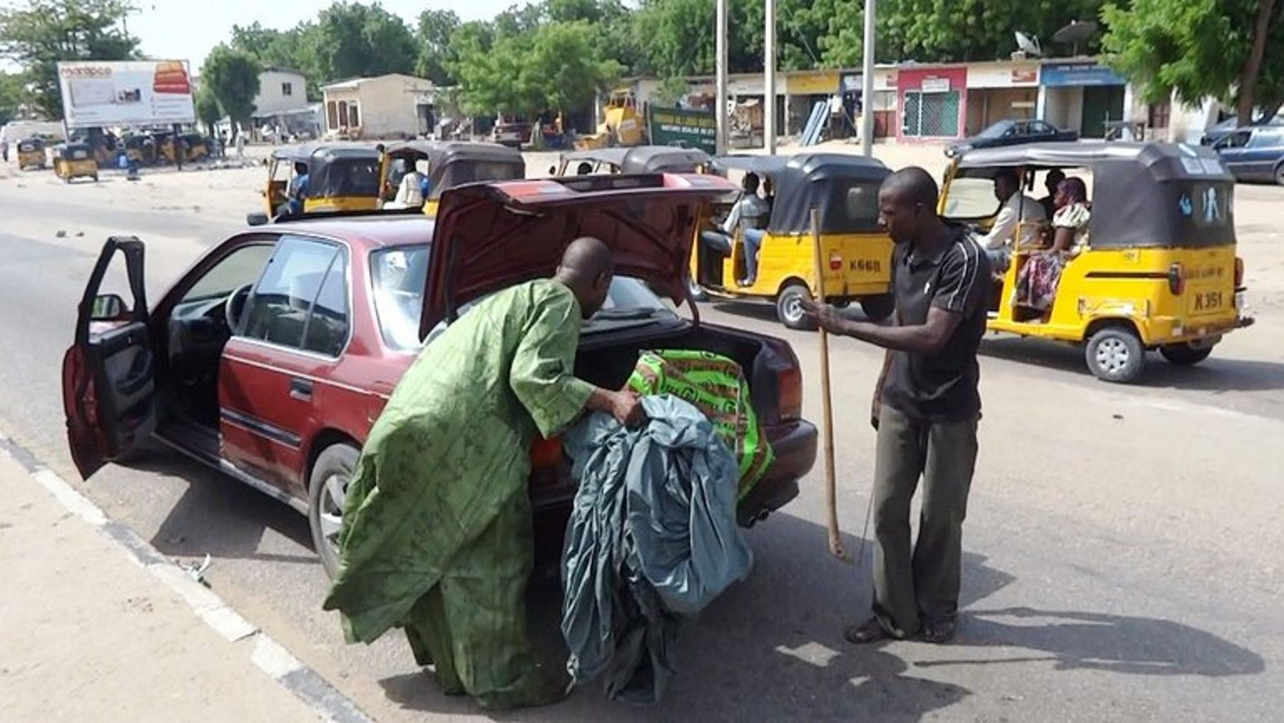 A vigilante peers into the trunk of a car looking for weapons on July 19, 2013 in Maiduguri, where Boko Haram has carried out most of its deadly attacks.