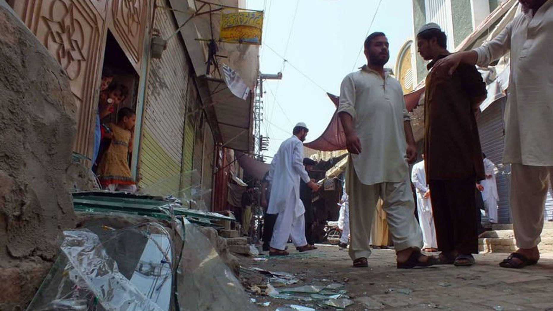 Local residents gather near the site of a bomb explosion in the northwestern town of Bannu on September 5, 2013. Gunmen attacked a mini-bus and two other vehicles near Pakistan's northwestern city of Peshawar late on Friday, killing nine people, police said.